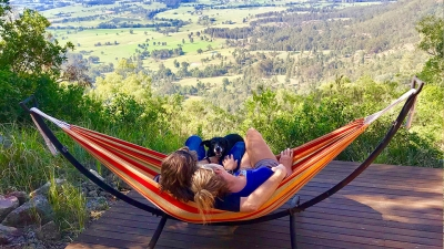 Two people sat in hammock on deck with dog and view of valley below