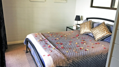 Bedroom with bed scattered with rose petals